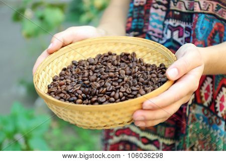 Woman holds in hands wattled basket with roasted coffee beans