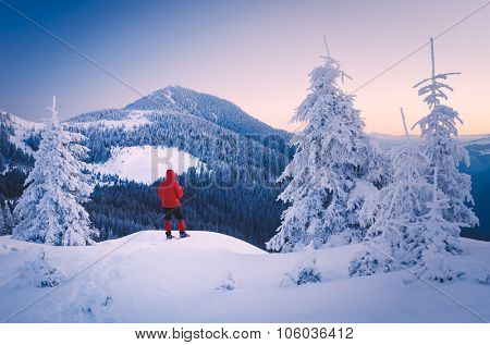 Winter landscape in the mountains. Tourist in a red jacket on a hill. Carpathians, Ukraine, Europe. Low contrast. Color toning