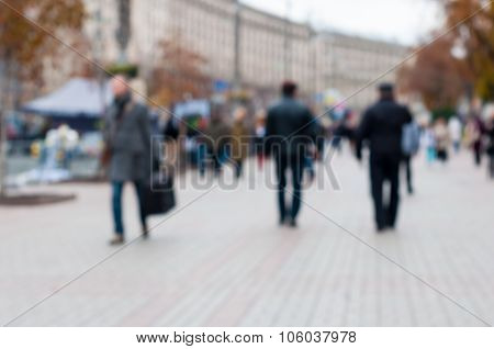Blurred crowd of anonymous people walking on busy street, city background
