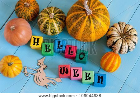 Halloween wooden blocks with many-coloured pumpkins and decor against an old wood background