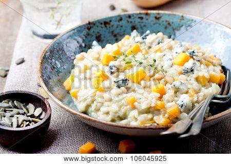 Pumpkin, blue cheese risotto in a ceramic plate