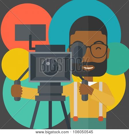 An african-american cameraman with beard and glasses looking through movie camera on a tripod vector flat design illustration. Square layout.