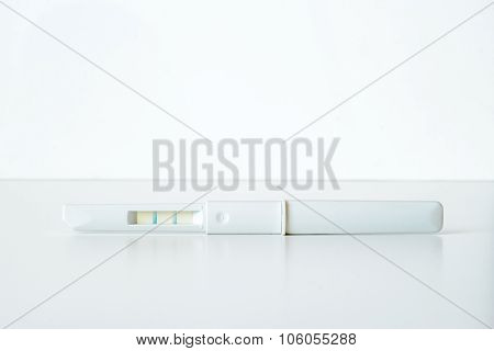 White plastic positive pregnancy test on white background