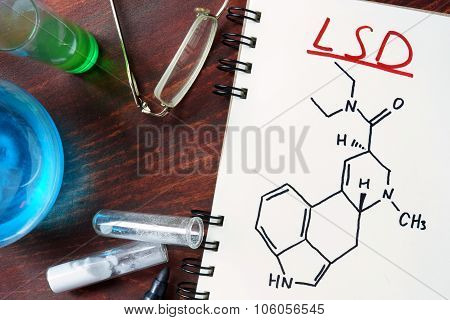 Notepad with chemical formula of LSD on the wooden table.