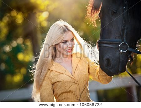Fashionable lady with yellow coat near black horse in forest. Beautiful young blonde woman and horse