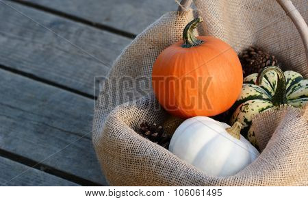 Small Gourds Nestled In Hessian On Wide Wooden Planks