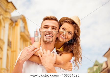 Happy Young Man Piggybacking His Beloved On Street