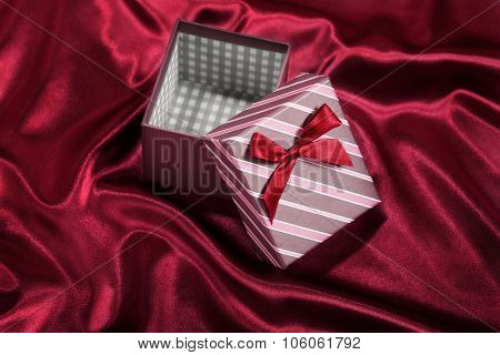 Empty gift box with red ribbon on red background