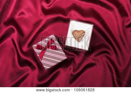 Gift box with chocolate candy heart on red