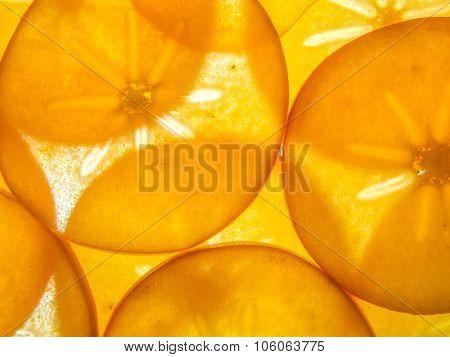 background of back lit ripe kaki persimon slices arranged