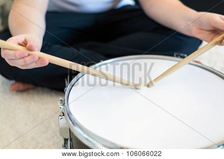 Boy teenager playing drums in  room