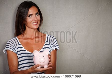 Happy Youngster Smiling While Holding A Piggy Bank