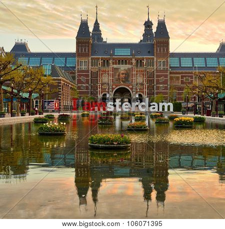 AMSTERDAM, NETHERLANDS: MAY 03: Frontal view of the Rijksmuseum (State Museum) with billboard of Rembrandt with its pond reflection at sunrise in Amsterdam, Holland on May 03, 2015