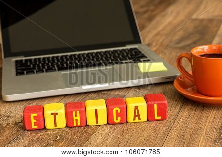 Ethical written on a wooden cube in front of a laptop