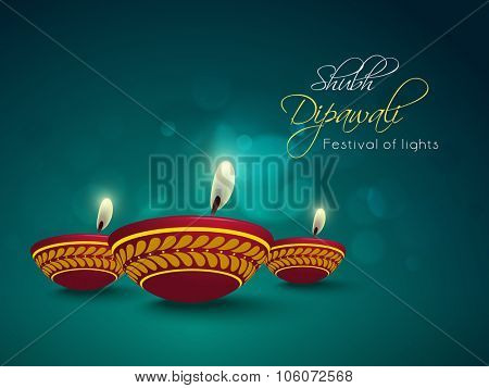 Floral decorated illuminated oil lit lamps on shiny background for Indian Festival of Lights, Happy Diwali celebration.