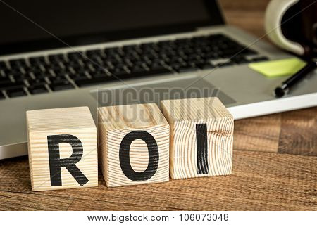 ROI (Return on Investment) written on a wooden cube in front of a laptop