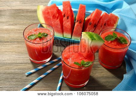 Glasses of watermelon juice on wooden table, closeup