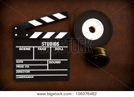 Movie Clapper Board And Film Reels Detail On Wooden Floor