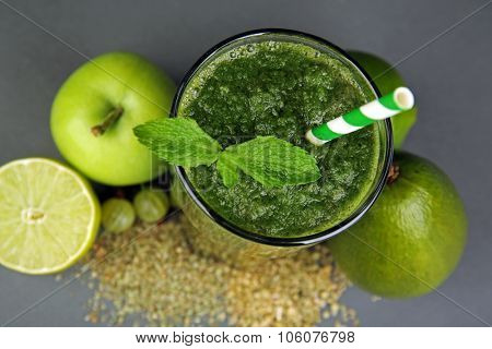 Green healthy juice with fruits and spices on gray background