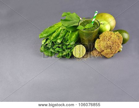 Green healthy juice with fruits and vegetables on gray background