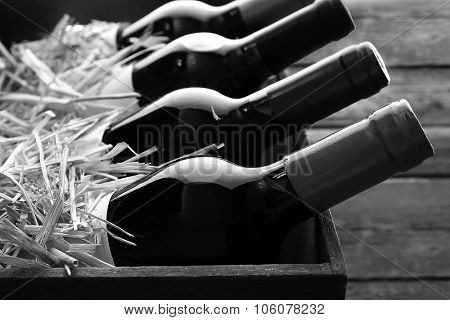 Box with straw and wine bottles,  black and white retro stylization
