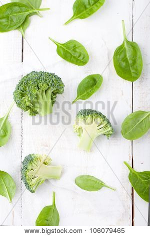 Broccoli and baby spinach on a white background.