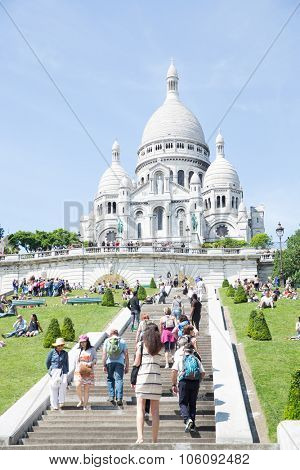 PARIS - JUNE 22: Unidentified tourists visiting Sacre Coeur Cathedral on Montmartre on June 22, 2014 in Paris. Sacre Coeur Cathedral is a Roman Catholic church, dedicated to the Sacred Heart of Jesus.