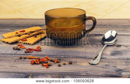 On The Wooden Table Is A Glass Cup Of Soup With Parsley