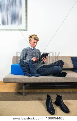 Young man, lounging on a sofa against some pillows in a living room, his shoes off, placed on the carpet in front of the couch, leisurely surfing on a portable tablet with touch screen