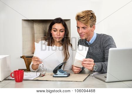 Young couple, comparing, filing and sorting out their personal finance situation, paying bills, and archiving tax return forms,  comparing and balancing their checkings account