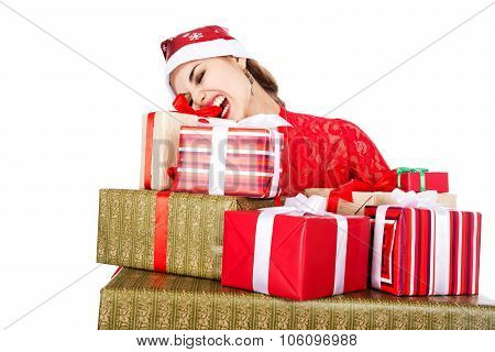 Young Girl In Santa Hats Teeth Trying To Open A Box With A Gift