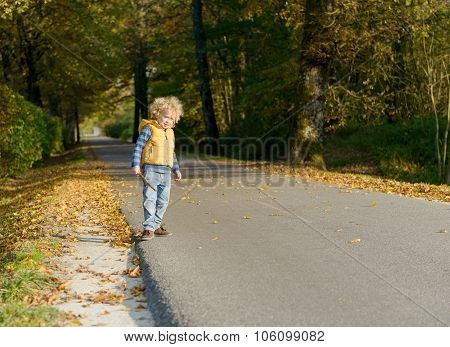 a little blond boy on the side of a small road,
