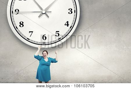 Middle aged stout woman in blue dress pointing at clock