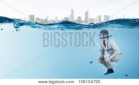 Young businessman in suit and diving mask jumping in water