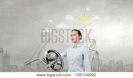 Young smiling pretty woman in drawn car with driving steering wheel