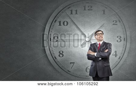 Middle-aged confident businessman in glasses and time concept