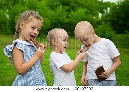 Happy kids eating chocolate bars outdoors in summer park