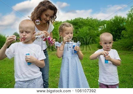 Mother with kids blowing bubbles in park