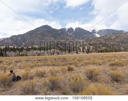 Backpacker Sits And Stares At Mountains At Great Sand Dunes National Park