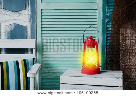 Vintage Red Lit A Kerosene Lamp On The Background Of The Old Painted Wall