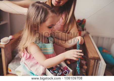 mother brushing toddler daughter's hair at home
