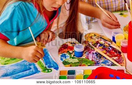 Close up of girl with brush painting on table in  kindergarten .