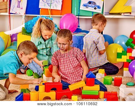 Group children male and female game blocks on floor in kindergarten .