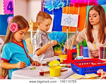 Children with teacher in  preschool  kindergarten painting.