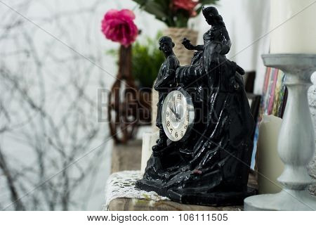 Black Statuette Of The Clock, Candlesticks With Candles On A Light Background With A Tree