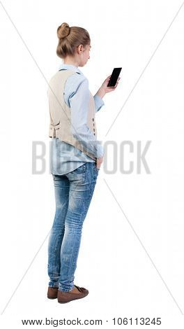 back view of standing young beautiful  woman  in vest and using a mobile phone. girl  watching. Rear view people collection.  backside view of person.  Isolated over white background.