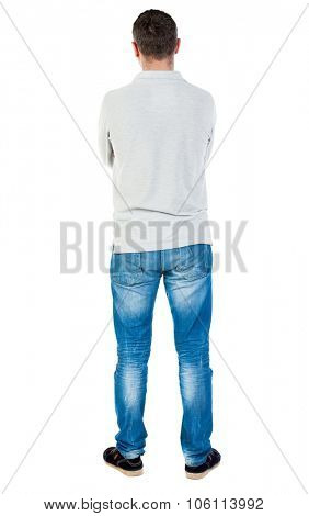 Back view of man in jeans. Standing young guy. Rear view people collection.  backside view of person.  Isolated over white background. A guy in a gray sweater standing with his arms crossed.