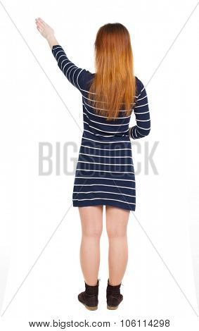 back view of woman. Young woman in vest presses down on something. Isolated over white background. Rear view people collection. backside view of person. she holds his hand open, palm forward.