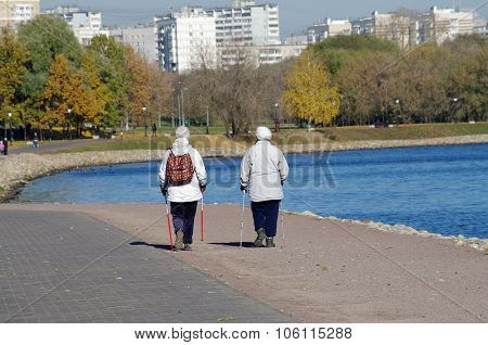 Older Women With Nordic Walking Sticks Walking In The Park Kolomenskoye On The Waterfront