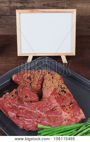 meat raw beef fillet chunk on black tray asparagus on wooden plate allspice pink peppercorn mustard name table  empty space for text